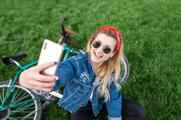 Dziewczyna siedzi na zielonej trawie na rowerze i bierze selfie na smartfonie