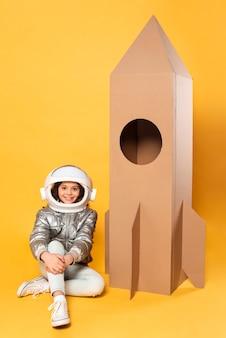 Dziewczyna siedzi obok statku kosmicznego kreskówki zabawki