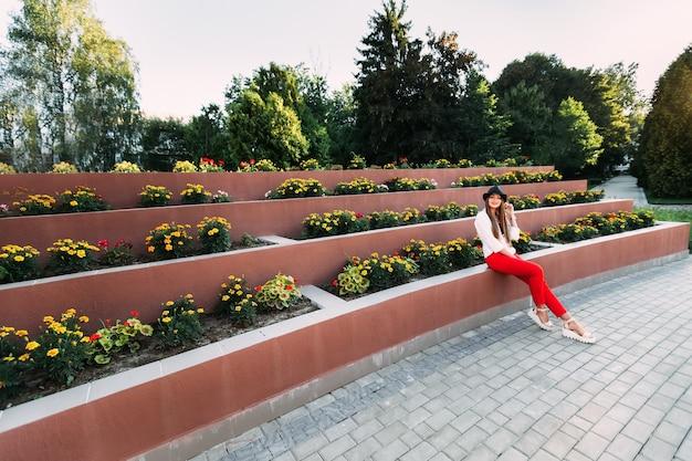 Dziewczyna siedzi obok wielopoziomowego klombu