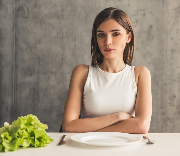 Dziewczyna siedzi przed pustym talerzem, sałata leży w pobliżu.