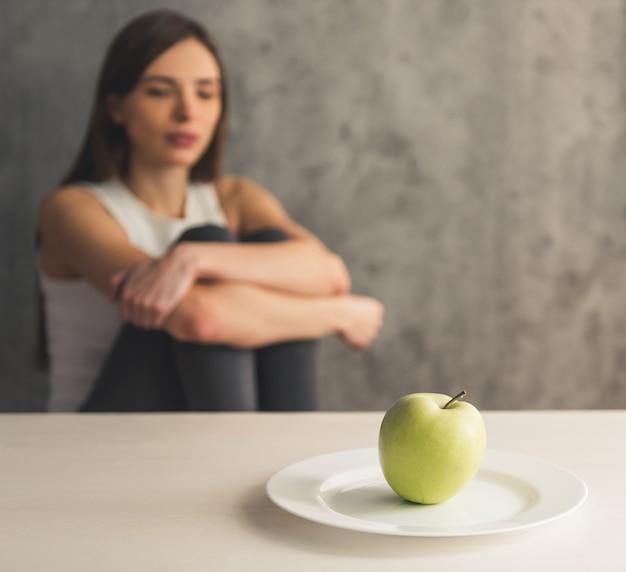 Dziewczyna siedzi przed talerzem z jabłkiem.