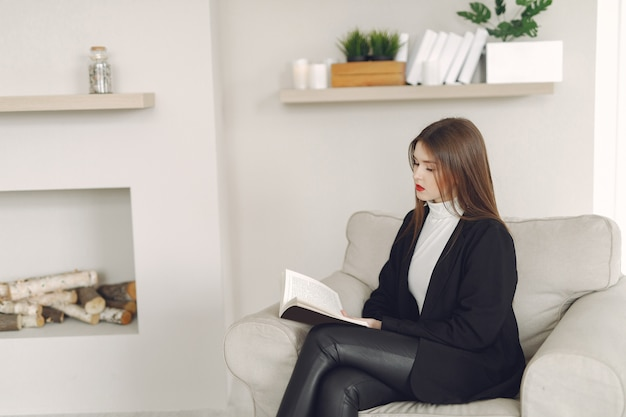 Dziewczyna siedzi przy hone na krześle i czyta książkę