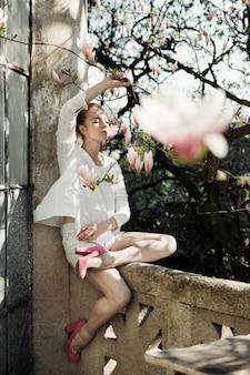 Dziewczyna siedzi przy kamiennym balustradzie, trzymając gałąź magnolii