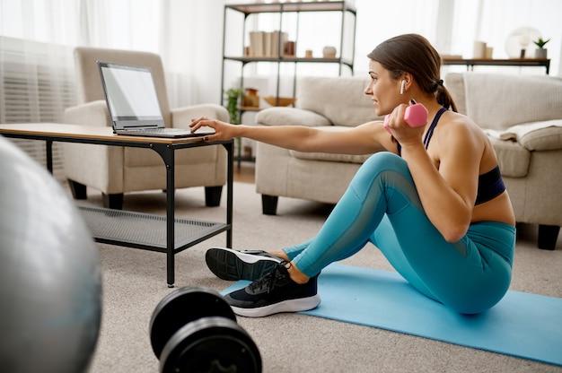 Dziewczyna siedzi przy laptopie, trening online fit
