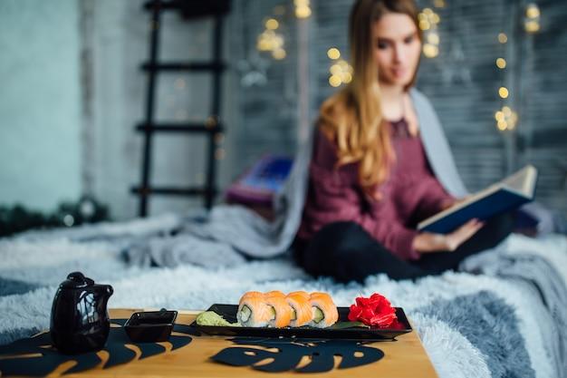 Dziewczyna siedzi przy łóżku z książką obok posiłku sushi