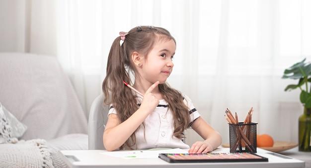 Dziewczyna siedzi przy stole i odrabia lekcje. dziecko uczy się w domu. nauka w domu. miejsce na tekst.