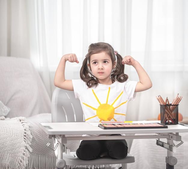 Dziewczyna siedzi przy stole i odrabia lekcje. dziecko uczy się w domu. nauka w domu