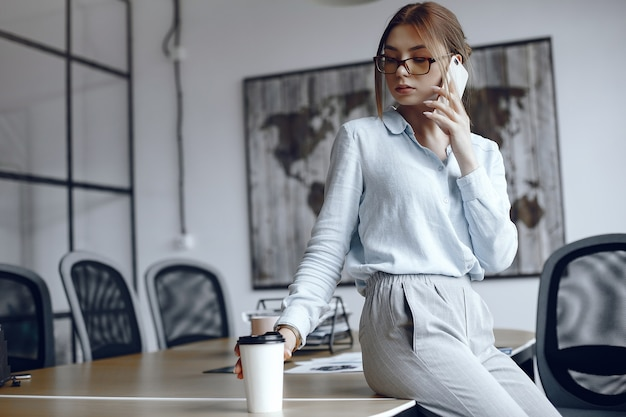 Dziewczyna siedzi przy stole. kobieta rozmawia przez telefon. brunetka pije kawę