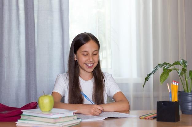 Dziewczyna siedzi przy stole pisze, czy jej praca domowa uczy się powrót do koncepcji szkoły