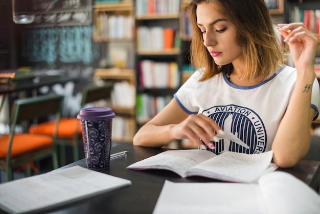 Dziewczyna siedzi przy stole z notebooków