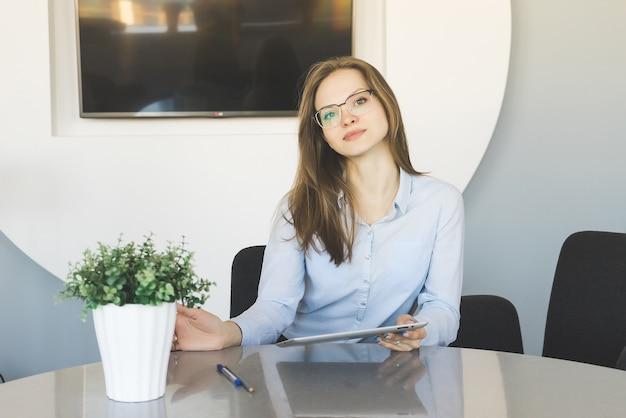 Dziewczyna siedzi przy stole z tabletem w rękach w biurze i patrzy na kamerę