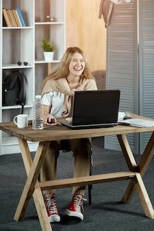Dziewczyna siedzi przy stoliku z laptopem i książkami, uśmiechając się niedbale
