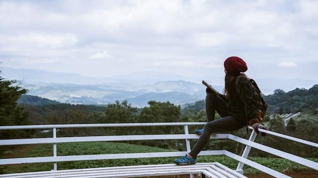 Dziewczyna siedzi relaksując się w naturalnym punkcie widokowym na góry.