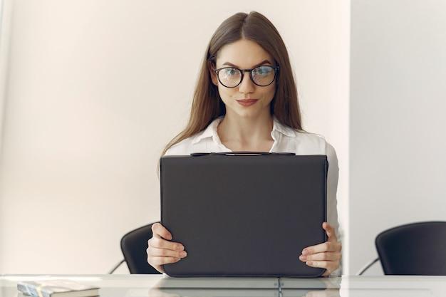 Dziewczyna siedzi w biurze z laptopem