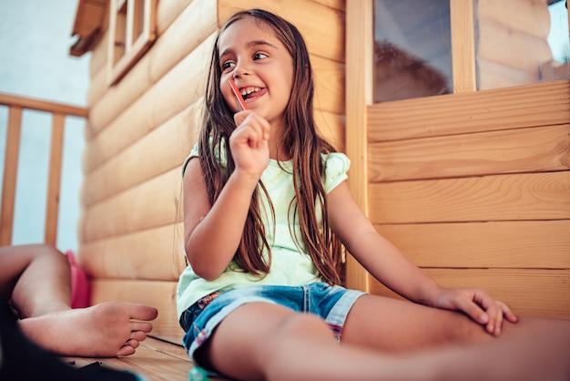 Dziewczyna siedzi w domku na drzewie i rysunek z kredki