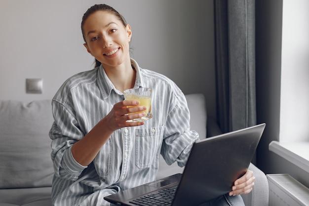 Dziewczyna siedzi w domu i korzysta z laptopa