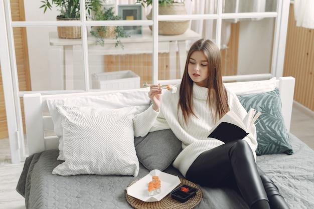 Dziewczyna siedzi w domu na kanapie z suszi