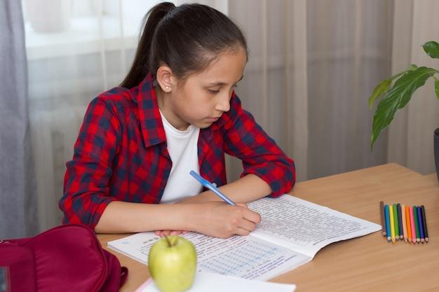 Dziewczyna siedzi w domu przy stole odrabia pracę domową powrót do koncepcji szkoły school