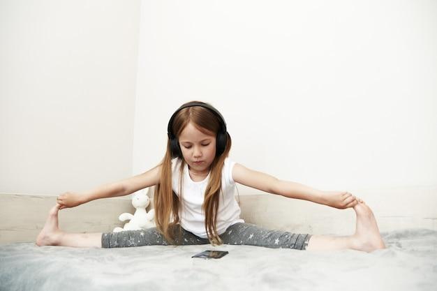 Dziewczyna siedzi w dużych słuchawkach i patrzy na ekran smartfona, siedząc na łóżku