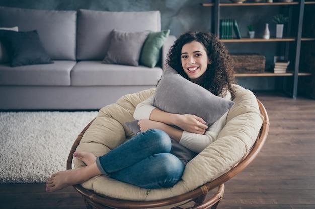 Dziewczyna siedzi w fotelu przytulanie poduszka w nowoczesnym loft industrialny ceglany styl wnętrza salonu