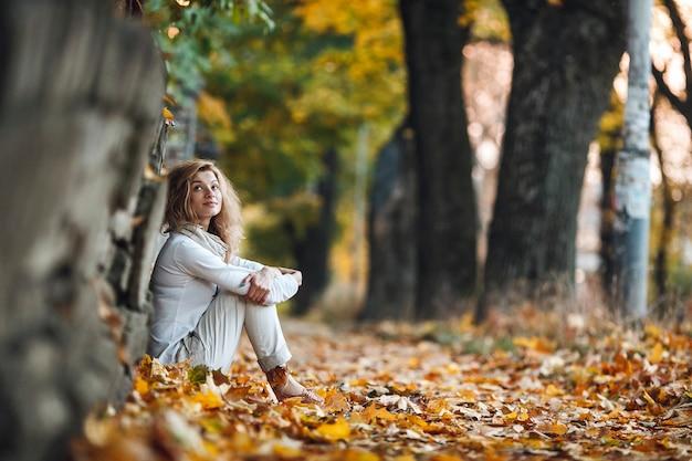 Dziewczyna siedzi w jesiennych liściach