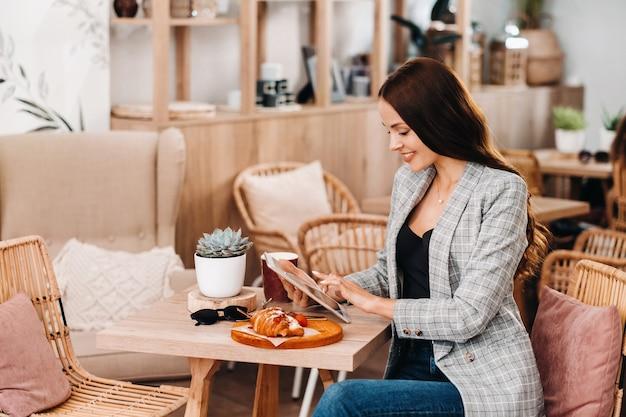 Dziewczyna siedzi w kawiarni i patrzy na tablet, dziewczyna w kawiarni się uśmiecha, praca na odległość