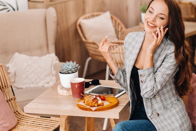 Dziewczyna siedzi w kawiarni i rozmawia przez telefon