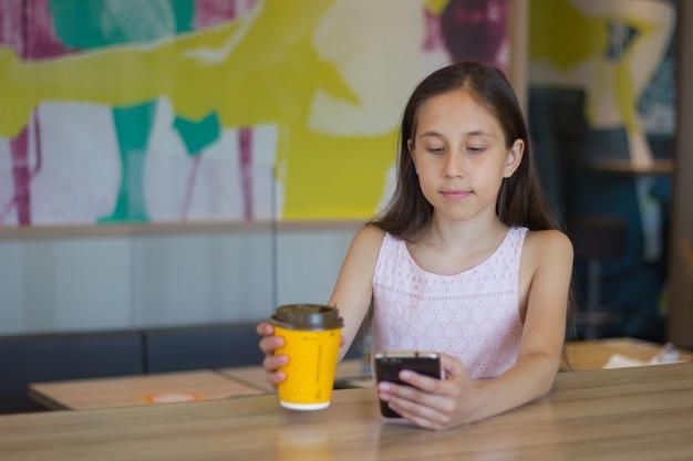 Dziewczyna siedzi w kawiarni, komunikując się w posłańcu, patrząc na mobilną szklankę herbaty z kawą w dłoni