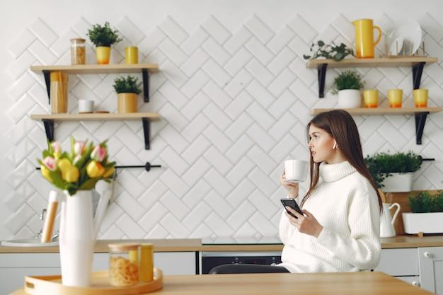 Dziewczyna siedzi w kuchni i picia kawy