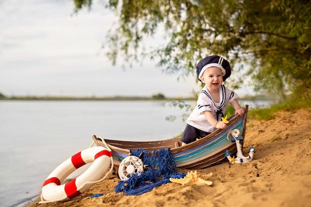 Dziewczyna siedzi w łodzi na piaszczystej plaży w pobliżu rzeki