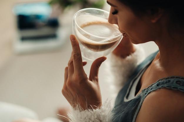 Dziewczyna siedzi wygodnie na kanapie i pije kawę