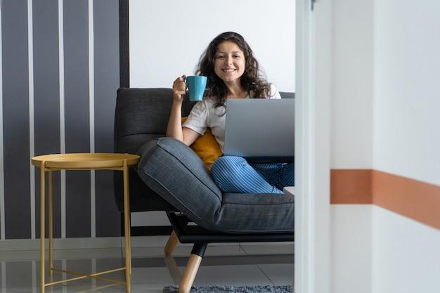 Dziewczyna siedzi z laptopem na kanapie w stylowym pokoju. praca w domu. atmosfera pracy dobry nastrój