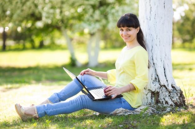 Dziewczyna siedzi z laptopem w pobliżu drzewa.