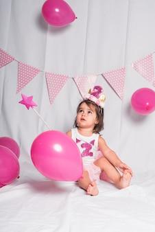 Dziewczyna siedzi z różdżką i różowymi balonami na białym tle.