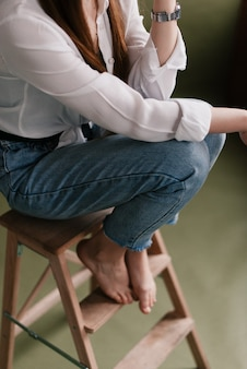 Dziewczyna siedzi ze skrzyżowanymi nogami. kolana damskie. oczekująca i relaksująca koncepcja, kolorystyka vintage.