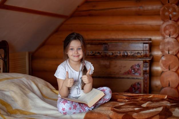 Dziewczyna siedzi ze skrzyżowanymi nogami z otwartą książką na kolanach i pokazuje kciuki do góry w sypialni