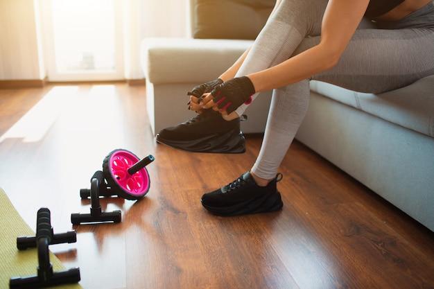 Dziewczyna siedzieć na kanapie i zawiązać sznurówki na trampki. przygotowanie do treningu sportowego w domu.