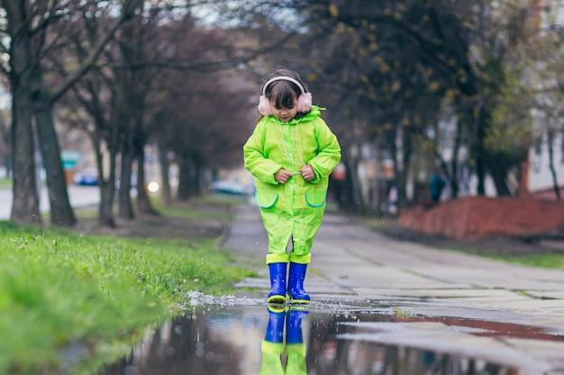 Dziewczyna skacze po kałużach w zielonym płaszczu i niebieskich butach na tle miasta i drzew po deszczu
