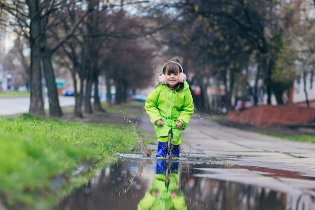 Dziewczyna skacze po kałużach w zielonym płaszczu przeciwdeszczowym i niebieskich butach