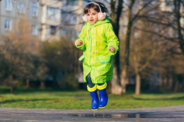 Dziewczyna skacze po kałużach w zielonym płaszczu przeciwdeszczowym