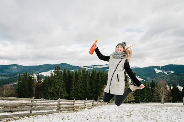 Dziewczyna skacze w śnieżną zimę, spacer w przyrodzie.