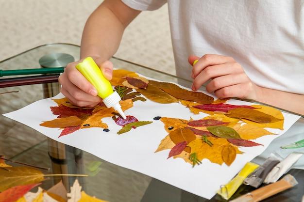 Dziewczyna składa aplikację z suchych liści. aplikacja dla dzieci na temat jesieni