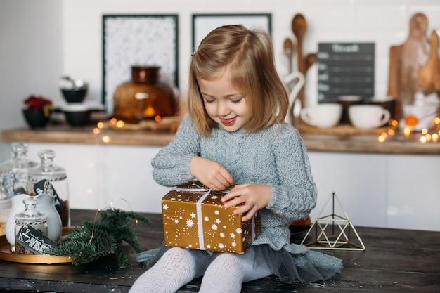 Dziewczyna śliczna z boże narodzenie prezenta pudełkiem w kuchni. wesołych świąt i wesołych świąt!