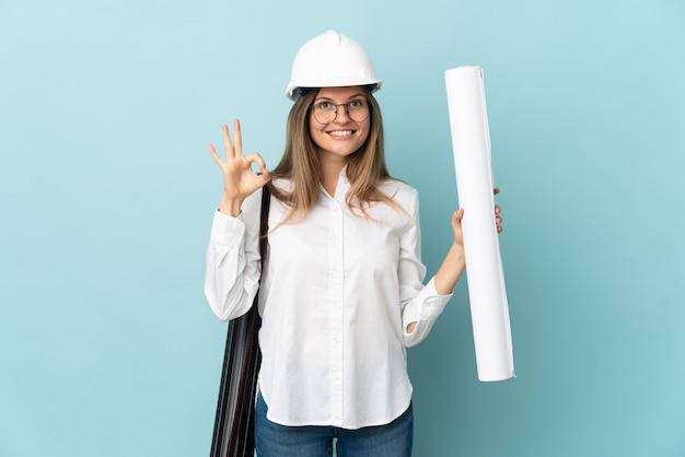 Dziewczyna słowackiego architekta trzymająca plany na białym tle na niebieskim tle pokazujące znak ok palcami