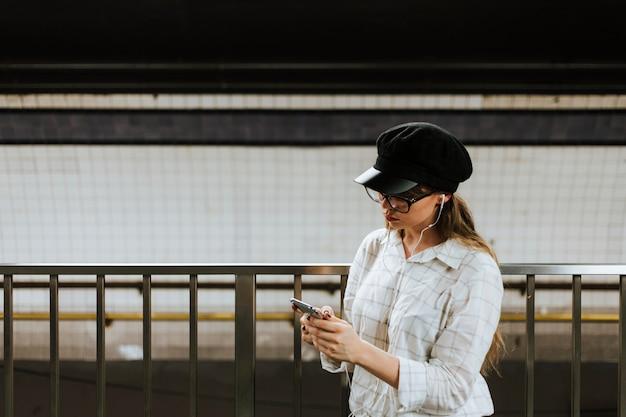 Dziewczyna słucha muzyka podczas gdy czekający pociąg