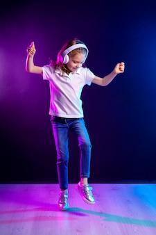 Dziewczyna słucha muzyka w hełmofonach na ciemnej kolorowej ścianie. tańcząca dziewczyna. szczęśliwa mała dziewczynka tańczy do muzyki. słodkie dziecko korzystających z szczęśliwej muzyki tanecznej.