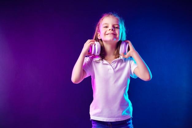 Dziewczyna słucha muzyka w hełmofonach na ciemny kolorowym. słodkie dziecko korzystających z szczęśliwej muzyki tanecznej i uśmiech pozowanie