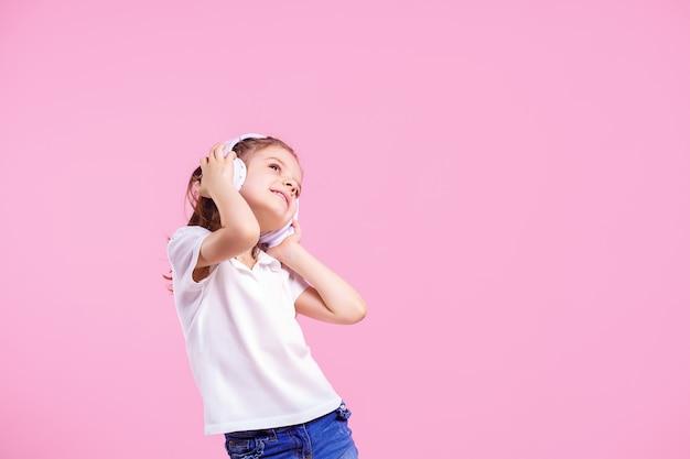 Dziewczyna słucha muzyka w hełmofonach na menchiach. słodkie dziecko korzystających z szczęśliwej muzyki tanecznej, zamknij oko i uśmiech pozowanie