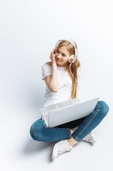 Dziewczyna słucha muzyki przez duże słuchawki i siedzi przy laptopie