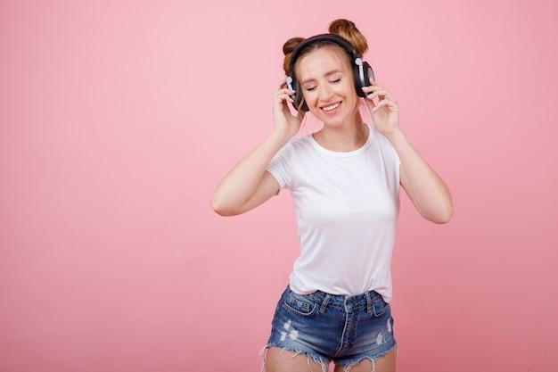 Dziewczyna słucha muzyki przez słuchawki i uśmiecha się na różowej przestrzeni